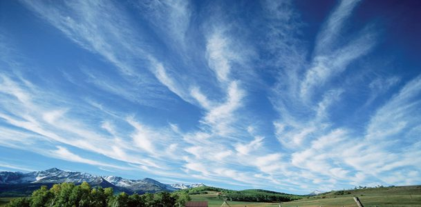 Feathery cirrus clouds drift across a deep blue sky over Colorado's San Miguel Mountains.
